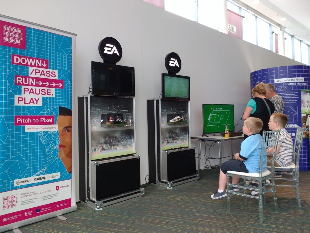 Kids and adults enjoying playing computer games in the Pitch to Pixel Pop-Up in the museum's Hall of Fame.
