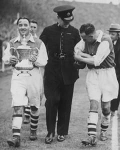 Alex James Arsenal Captain leaving the ground with the FA Cup after defeating Sheffield in the final at Wembley. Fellow player Joe Hulme attempts to untangle himself from a police officer who is guarding the cup. Picture via Mirrorpix.