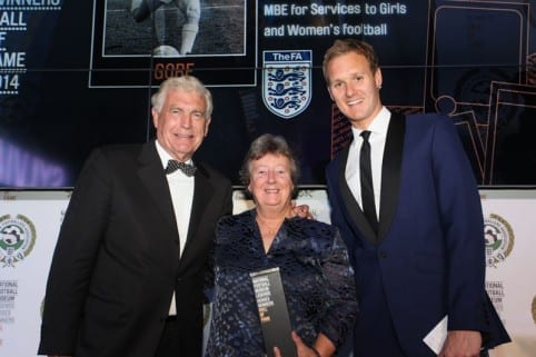 Sylvia Gore receives her National Football Museum Hall Of Fame award from Sir Trevor Brooking and host Dan Walker.