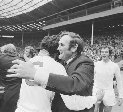 Revie was renowned for his man management skills and close bond with his players, demonstrated here with Norman Hunter after their 1972 FA Cup final victory. Image via Mirrorpix.