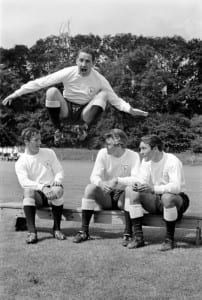 Members of the Tottenham Hotspur team training.  Dave Mackay jumping high as teammates sit on the bench talking July 1965. Pic via Mirrorpix.