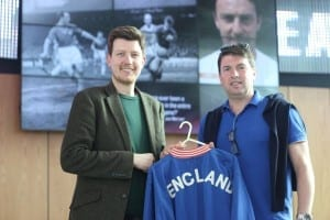 National Football Museum Exhibitions Co-Ordinator Jon Sutton accepts the Bobby Moore tracksuit from Paul.
