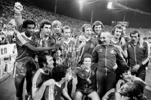 European Cup Final at the Olympic Stadium in Munich.  Nottingham Forest 1 v Malmo 0. Only some 27 months after languishing in eighth place in the Second Division, Nottingham Forest are champions of Europe. Partying beside the pitch at the Olympic Stadium after beating Malmo are, standing left to right, Viv Anderson, Peter Shilton, sub Chris Woods, John McGovern, Ian Bowyer, sub David Needham, trainer Jimmy Gordon, Trevor Francis, Frank Clark (nearly hidden) and sub John Crouching are Larry Lloyd, John Robertson, Tony Woodcock and Garry Birtles with Kenny Burns in a headlock. 30th May 1979. Pic via Mirrorpix.