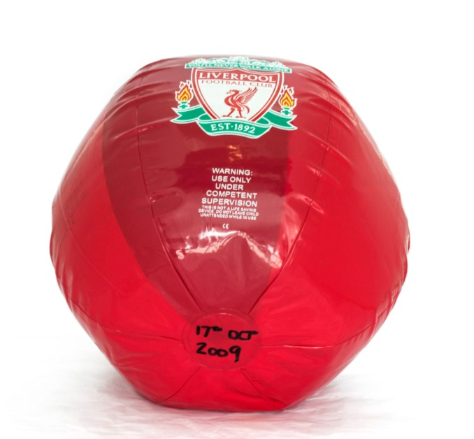 """a red beach ball with warning on it """"use only under competent supervision"""""""