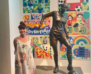 Artist Billy stands with Lily Parr statue with her colourful artwork behind